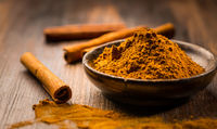 Cinnamon powder in wooden bowl with cinnamon sticks on wooden background as cooking and baking ingredient.