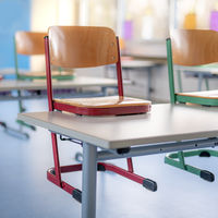Red chair in a classroom stands on a table against a blurred background
