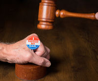 I voted by mail campaign button or sticker on hand with a gavel and mallet to illustrate lawsuits about voting