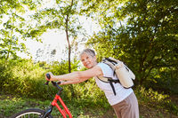 Vitale Seniorin beim Tretroller fahren in der Natur