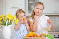 Mädchen pressen Saft aus frischen Orangen