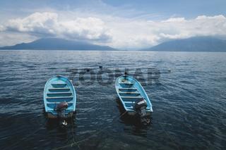 Two parallel swimming blue boats on lake Atitlan with view on volcanoes in Santa Cruz la Laguna, Guatemala