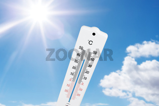 thermometer against blue summer sky and sun