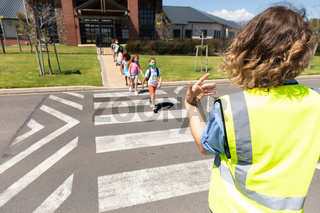 Group of kids wearing face masks crossing the road