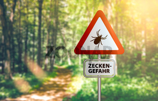 warning sign with text ZECKEN GEFAHR, German for beware of ticks, against defocused forest background