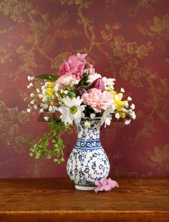Vase with flowers against wall with red vintage wallpaper