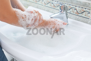 Close-up photo of woman washing hands with soap in sink at bathroom