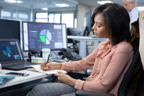 Businesswoman taking notes while sitting on her desk at modern office