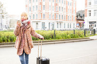 Winter Portrait with suitcase and smartphone