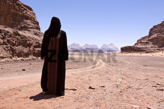 Nomadic woman with burka in the desert
