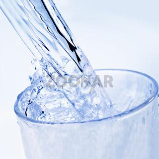 Wasser wird in ein Glas eingeschenkt