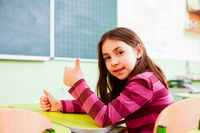 Primary schoolgirl with thumb up in empty classroom
