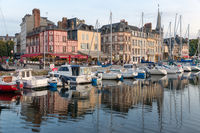 Harbor of historic city Honfleur with sailing ships and restaurants