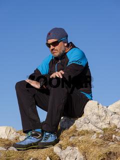 Bergsteiger, nachdenklich, auf einem Felsen