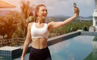 Cheerful sportswoman taking selfie on poolside