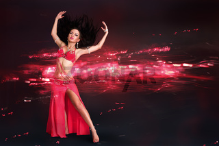 Young woman doing belly dance performance in exotic costume with abstract background behind her