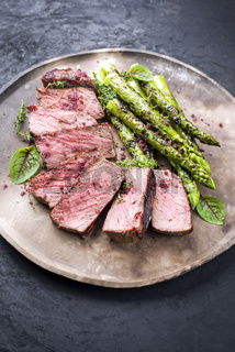 Barbecue dry aged wagyu roast beef steak with green asparagus and lettuce offered as close-up on a rustic modern design plate