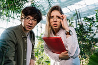 Young agricultural engineers working in big greenhouse