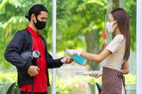 Restaurant waitress push hand sanitizer gel for delivery man.