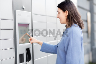 smiling woman using automated parcel machine
