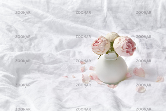 Vase with fresh roses on crumpled sheets.