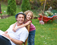 Tochter umarmt Vater im Garten