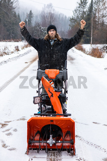 Young man playing with a snowplough in the winter