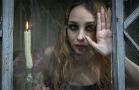 Beautiful sad young girl looking out the window with a candle