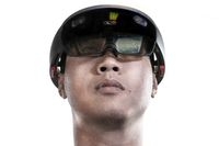 Low view portrait of asian man experiences Mixed reality with HoloLens 1 on white background. Future advanced technology concept