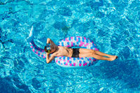 Boy relaxing on air mattress in the swimming pool - top view