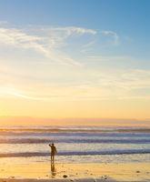 Surfer ocean beach sunset background