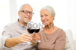happy senior couple with glasses of red wine