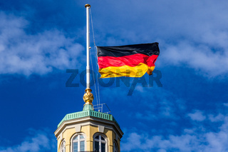 Detail view on German Flag at Halfmast, auf Halbmast, on the tower roof of Castle Karlsruhe, blue sky in background. Germany