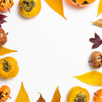 Halloween concept. Pumpkin and autumn leaves, sweet persimmon fruit on white background. flat lay, top view, copy space