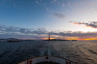 Amazing colorful sunset over Norwegian sea seen from small cruise ship MS Lofoten of Hurtigruten on clear winter day