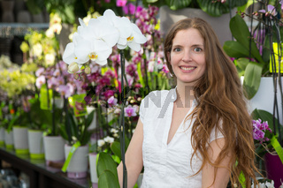 Customer in flower shop posing with orchid