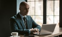 Bald middle aged businessman in business suite working on laptop next to open windows in modern office. Handsome bold man working on laptop in office