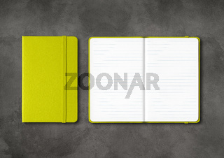 Lime green closed and open lined notebooks on dark concrete background