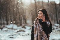 Woman talking on mobile phone. Smiling girl talking on mobile phone in cold winter day.