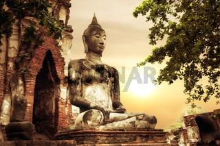 Buddha at Wat Mahathat ruins under sunset sky. Ayutthaya, Thailand travel landscape and destinations