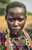 TOPOSA TRIBE, SOUTH SUDAN - MARCH 12, 2020: Woman from Toposa Tribe wearing traditional colorful beads and piercing and looking at camera in South Sudan, Africa