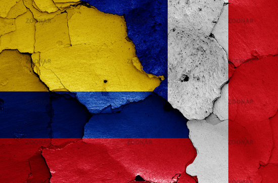 flags of Colombia and France painted on cracked wall