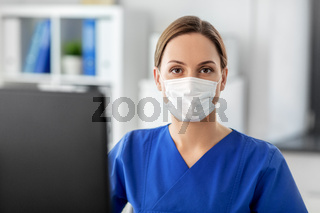 doctor or nurse in mask with computer at hospital