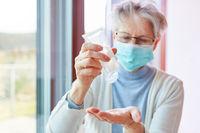 Seniorin in Quarantäne mit Desinfektionsgel auf Hand