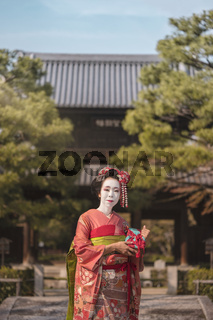 Maiko in a kimono posing in Kyoto on a stone bridge in front of the gate of a traditional Japanese kennin temple surrounded by pine trees.