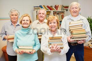 Gruppe Senioren mit vielen Büchern in der Bibliothek der Seniorenresidenz