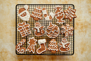 Fresh baked Christmas shaped gingerbread cookies placed on steel grill