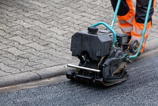 vibratory plate compacts asphalt