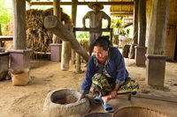 Local woman controls the husking of rice grains, Ban Phong Van close to Luang Prabang, Laos