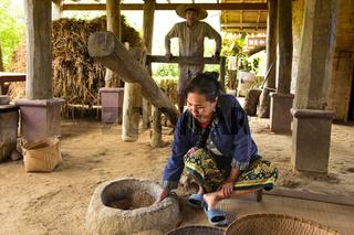 Einheimische Frau kontrolliert das Schälen der Reiskörner mit einem manuell betriebenen Holzhammer in einem Steintrog